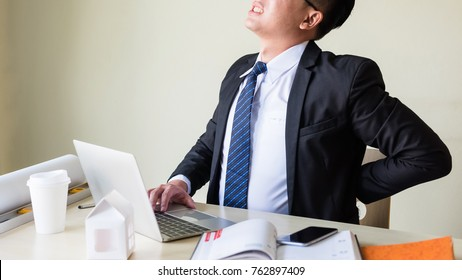 young Asian businessman manager with black suit and neck tie getting painful feelings and sitting at working table in office while holding his back. Business man trouble of office syndrome.