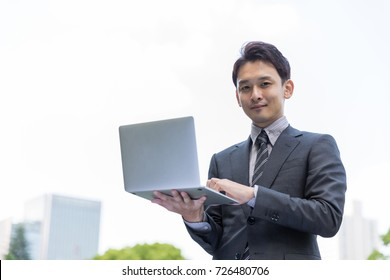 young asian businessman in park