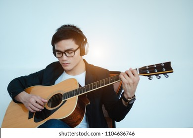 Young Asian businessman are playing the guitar and are recording at studio,with copy space.The concept of music business.Relaxation from work.Startup business.Artist,Inspirational