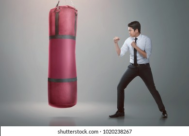 Young asian businessman punching boxing bag over gray background