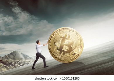 Young asian businessman pushing golden bitcoin climbing the hill with sky background