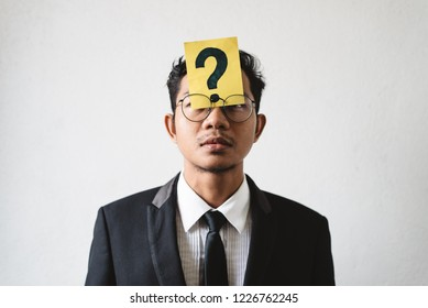 Young Asian businessman with QUESTION MARK on his forehead. Concept of business solution, planning and problems