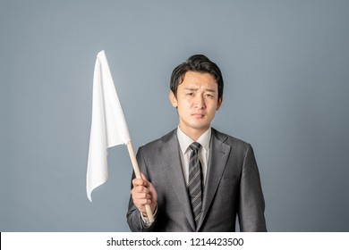 Young asian businessman showing a white flag.