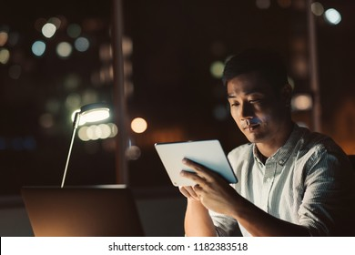 Young Asian businessman sitting at his desk using a digital tablet while working in a dark office at night with city lights in the background