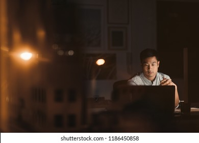 Young Asian businessman sitting at his desk working on a laptop late at night by office windows reflecting city lights