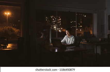 Young Asian businessman sitting at his desk working on a laptop in a dark office at night with city lights in the background