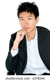 A young Asian businessman sitting in an office chair on white background