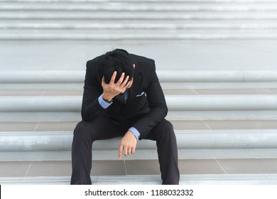Young asian businessman sitting on concrete stairs and holding head with hand are stressed with work and life issues. He thinks to commit suicide when he know business is failing and unemployed.