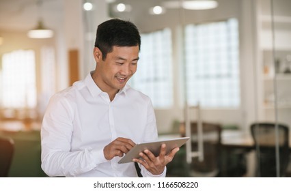 Young Asian businessman smiling while standing alone in a large modern office working online with a digital tablet