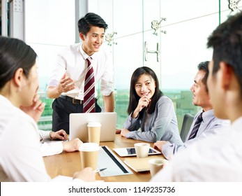 young asian businessman speaking to coworkers during meeting in modern office.