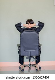 A young Asian businessman is stressed sitting on a chair.