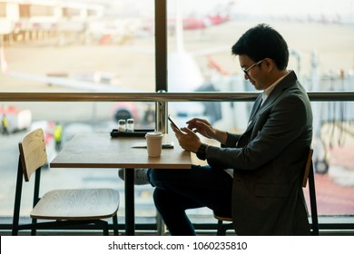 Young asian businessman with suits standing looking at airplane and hold a cup of hot coffee while using smartphone at waiting area in international airport