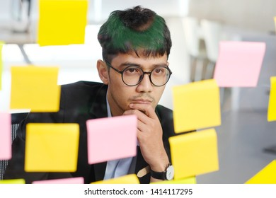 Young asian businessman thinking while reading sticky notes at office, business brainstroming creative planing ideas to success in business concept
