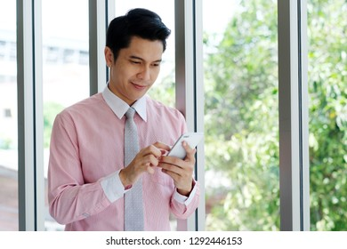 Young asian businessman using smart phone at office , business people on phone, office life, technology and lifestyle