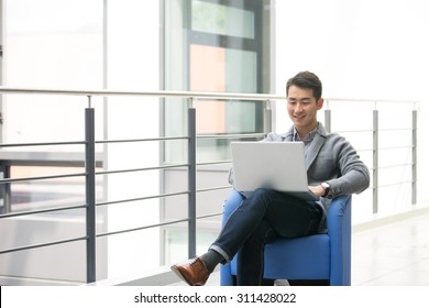 Young asian businessman using tablet, mobile phone in the office