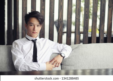 A young Asian businessman is waiting for a partner in a cafe. A Korean young man talking on the phone in a cafe.