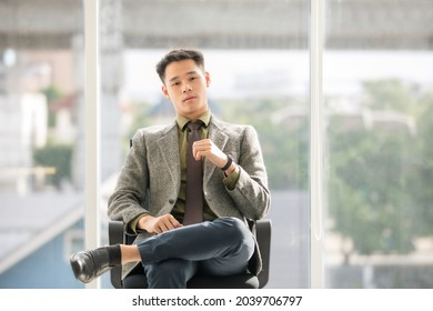 Young Asian businessman wear gray suit olive green shirt and dark brown tie. Sit on chair, cross legs, look at the camera in large glass room, bright, blurred background city view. Modern style