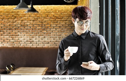 The Young Asian Businessman Wearing Black Shirt and Eyeglasses Use Smart Phone and Hold a Cup of Coffee