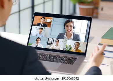 Young Asian businessman work at home and virtual video conference meeting with colleagues business people, online working, video call at home office