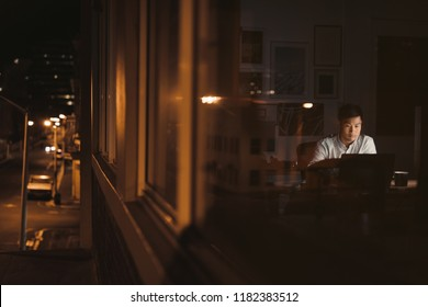 Young Asian businessman working at his desk late at night behind office building windows reflecting the city