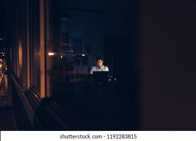 Young Asian businessman working at his desk late at night behind office building windows reflecting city lights