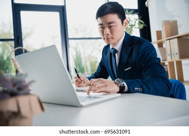 young asian businessman working with laptop
