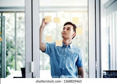 Young Asian Businessman Working in Office Meeting Room. Man Analyzing Data Plans and Project. Concentrate on Document Note on Board