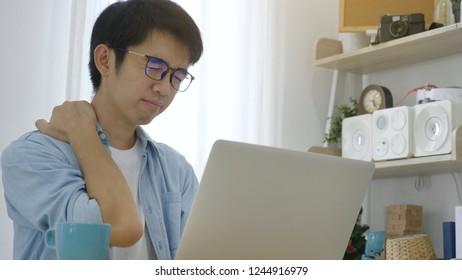 Young Asian businessman working on laptop at office, feeling tired and having shoulder pain
