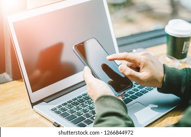 Young Asian businessman is working on smart phone in office with laptop. Online shopping.