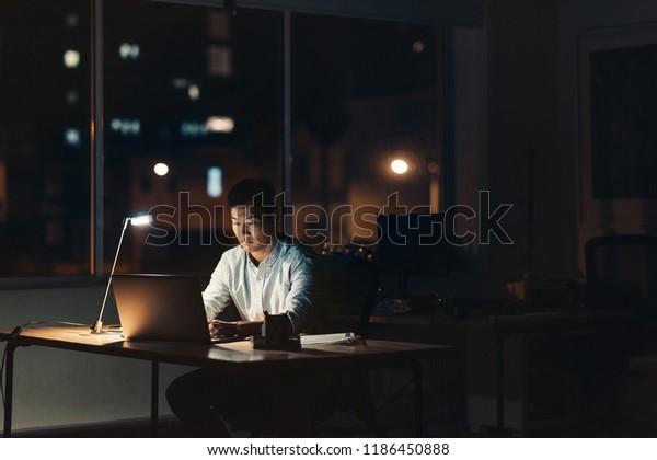 夜、暗いオフィスの机に座りながら、背景に街灯を持つノートパソコンを使用するアジア系の若いビジネスマン