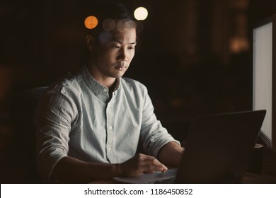 Young Asian businessman working online at his desk in an office late at in the evening with city lights glowing in the background