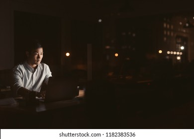 Young Asian businessman working overtime alone at his desk in an office late at night with city lights glowing in the background