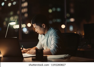 Young Asian businessman writing in a notebook while working at his desk in a dark office at night with city lights in the background