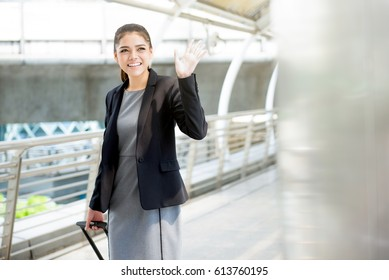 Young Asian businesswoman with baggage waving hand bye bye at the airport - business travel concept