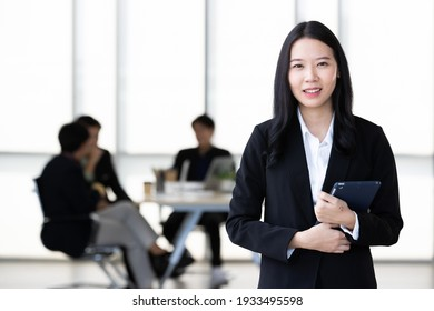 Young Asian businesswoman in black suit standing and holding tablet  computer posing to camera in office with her team talking in blur background.