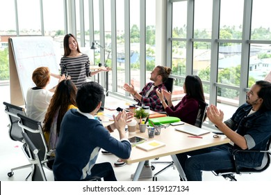 Young asian businesswoman explain idea to group of creative diverse team at modern office. Manager standing against rear view of multiethnic people. Audience applauding speaker after presentation.