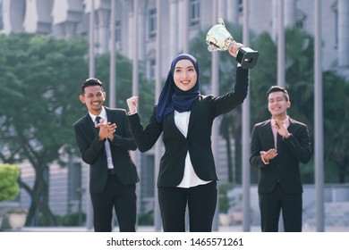 Young asian businesswoman and with her team winning a gold trophy. Successful business team rewarded .Winning business team concept. Womens Power. Great working woman achieve goal successful.