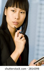 A young asian businesswoman holding a PDA with stylus (shallow depth of field)