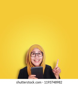 Young Asian businesswoman holding tablet, having an i dea gesture. Close up body portrait. Orange Background