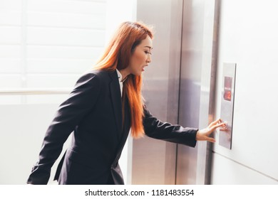 Young Asian businesswoman in hurry rush hour pressing an elevator button
