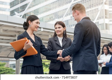 Young asian businesswoman introduces herself to client.