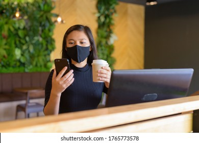 Young Asian businesswoman with mask using phone and sitting with distance inside the coffee shop