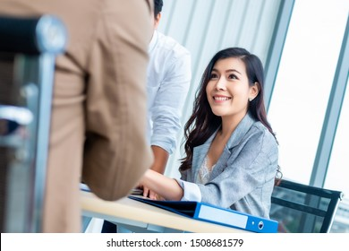Young asian businesswoman meeting and advising with her team in the office.