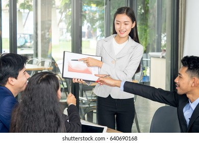 Young asian businesswoman with presentation during business meeting at cafe, financial report, presentation chart, business presentation and teamwork concept
