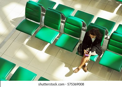 Young asian businesswoman sitting alone at airport waiting area holding her passport waiting for boarding an airplane. Shot from top view or above.