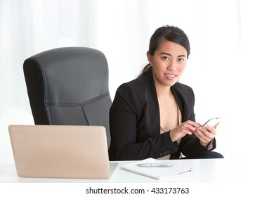 Young asian businesswoman sitting at desk in office typing on smartphone