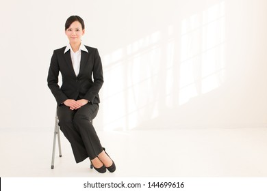 young asian businesswoman sitting on white room