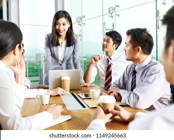 young asian businesswoman speaking to teammates during meeting in modern office.