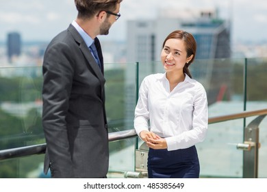 Young Asian Businesswoman Talking to Colleague