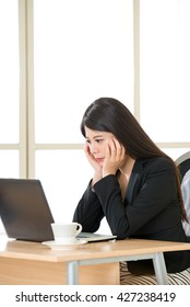 Young Asian businesswoman thinking and Staring at Computer Screen in office